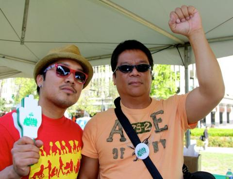 Armael Bulawin Malinis and Edgardo Pichay, male allies and community organizers at Migrante International, an advocacy group that defends the rights and welfare of overseas Filipino workers, raise their fists in solidarity with the rights of home care workers.